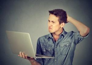 Funny clueless dumb guy having troubles with his laptop. Complicated technology concept